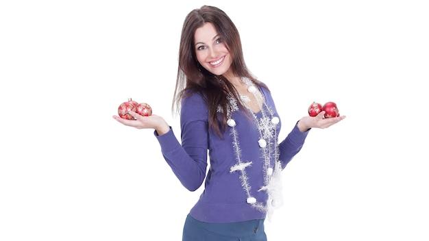 白で隔離のクリスマスボールを示す非常に幸せな若い女性