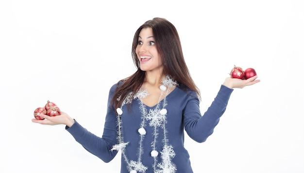 クリスマスボールを見せてとても幸せな若い女性。
