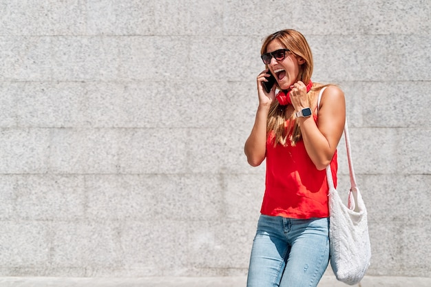 市内で彼女の携帯電話で話している非常に幸せな若い女性
