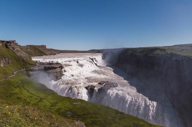 Очень высокий и красивый водопад в исландии. сказочный водопад в зеленых долинах прекрасного острова исландия