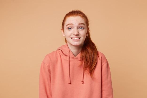 Una donna dai capelli rossi molto insicura che guarda dritto con modestia
