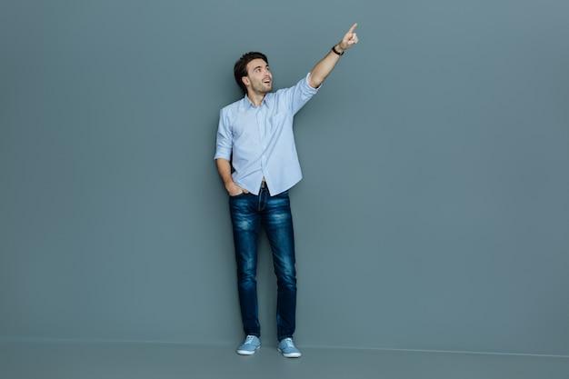 とても興味深い。灰色の背景に立っている間笑顔で彼の手の方向を見ている幸せな素敵なハンサムな男