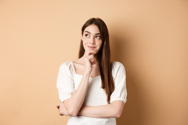 Very interesting. pensive cute girl thinking and looking at upper left corner logo, smiling pleased, having good idea, standing on beige background