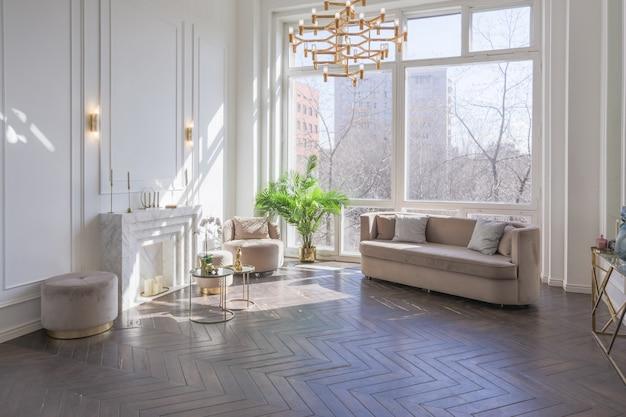 ゴールドのメタリック要素を備えたシックなソフトベージュの家具、床への大きな窓、木製の寄木細工が施された豪華で居心地の良いリビングルームの非常に明るく明るいインテリア