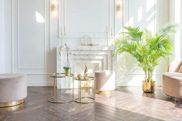 Очень светлый и светлый интерьер роскошной уютной гостиной с шикарной мягкой бежевой мебелью с золотыми металлическими элементами, огромным окном в пол и деревянным паркетом.