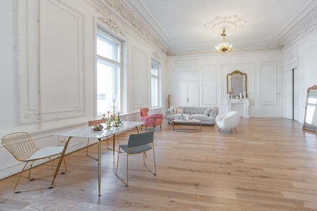 큰 거실의 매우 가벼운 바로크 스타일의 고급스러운 인테리어입니다. 멋진 치장 벽토로 장식된 흰색 벽. 골드 요소가 가미된 세련된 가구로 꾸며진 로열 스타일 아파트