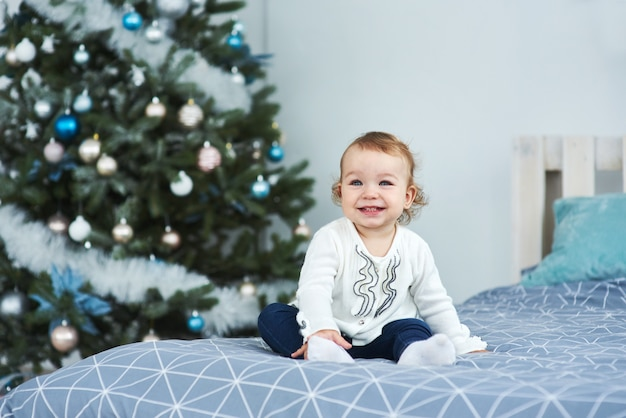 Very nice charming little girl blonde in white sitting on the bed and looking at the picture on the background of smiling christmas trees in bright interior of the house