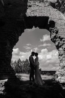 とても素敵な赤毛の若いちょうど結婚したばかりの幸せなカップルが屋外の夕日でキスしている