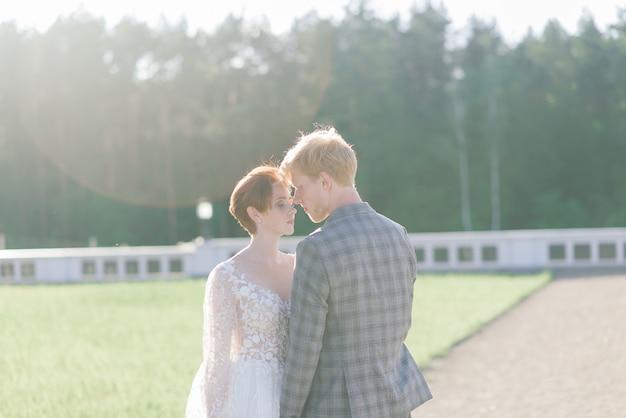 とても素敵な赤毛の若いちょうど結婚している幸せなカップルが屋外の夕日でキス