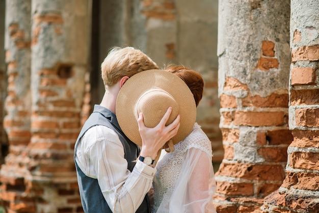 とても素敵な赤毛の若いちょうど結婚した幸せなカップルが屋外の夕日にキス