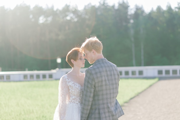Very nice redhead young just married happy couple kissing in the sunset outdoors