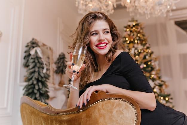 Очень милая женщина в черном платье с праздничным настроением, опираясь на спинку стула, на елочных игрушках