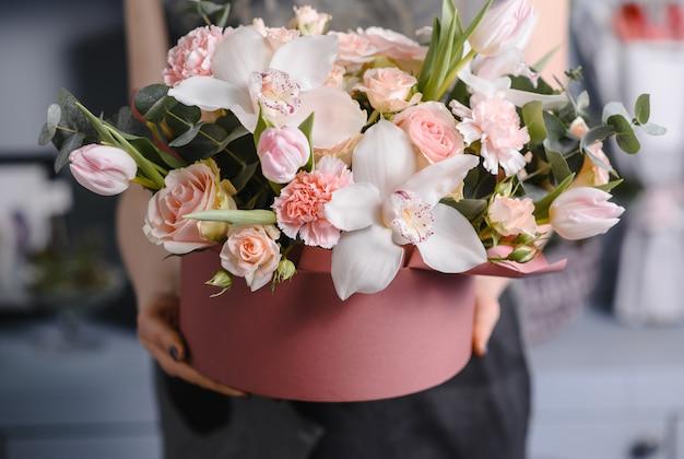 Очень милая молодая женщина держит большой и красивый красочный свадебный букет с фиолетовыми гвоздиками и матиолами