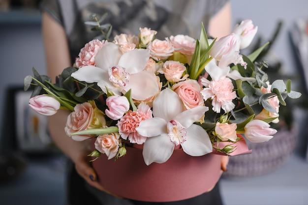 Очень милая молодая женщина держит большой и красивый красочный свадебный букет