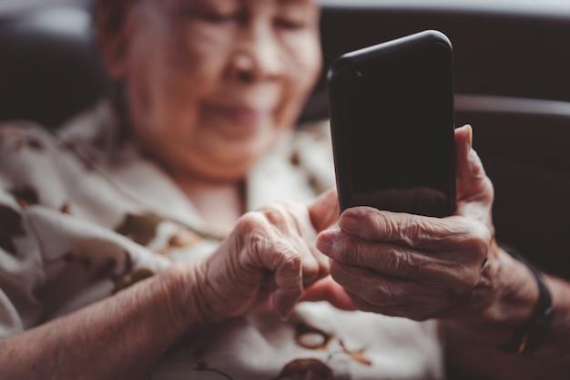 자동차로 여행하는 80-90 세 사이의 아주 오래된 아시아 인 승객 여성