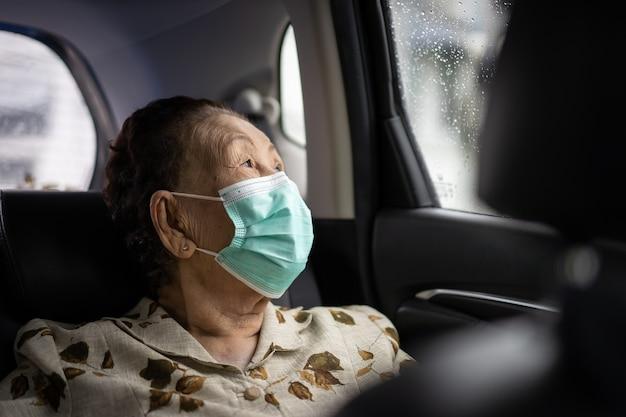 80-90 세 사이의 아주 오래된 아시아 여성 나이는 개인 차량으로 여행합니다.