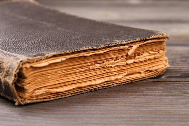 非常に古い本のクローズアップ。灰色の机の背景。