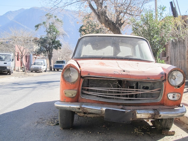 A very old car abandoned in the street