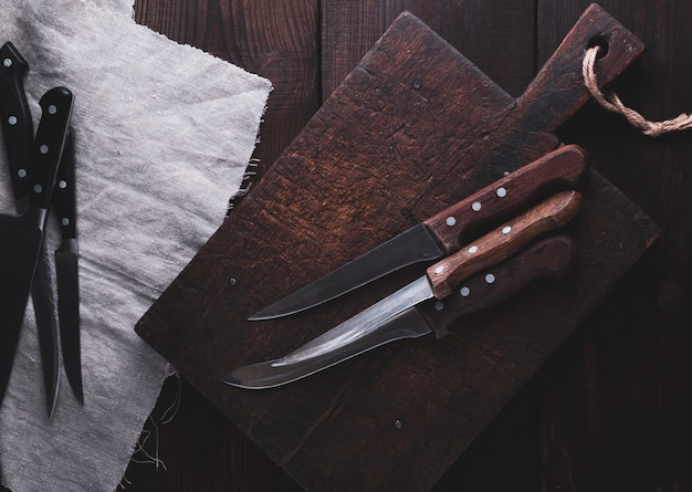 Very old cutting brown wooden board and kitchen knives