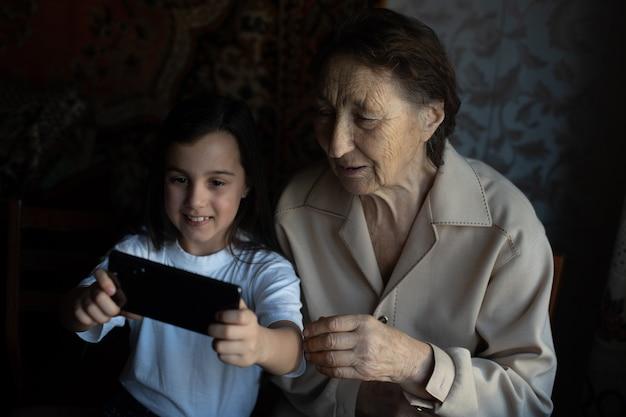 オンラインでスマートフォンを持っている非常に古い曽祖母と孫娘