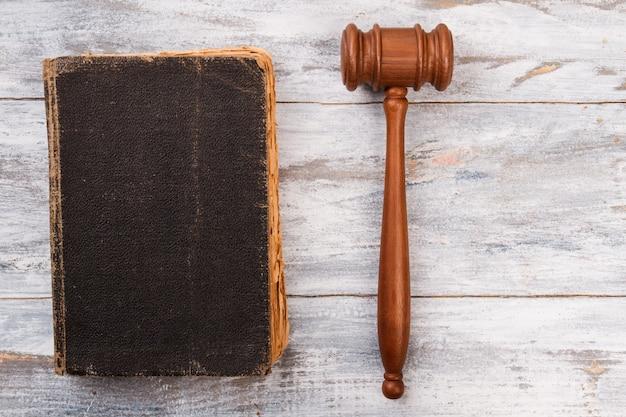 Очень старая книга закона и молоток на белом дереве.