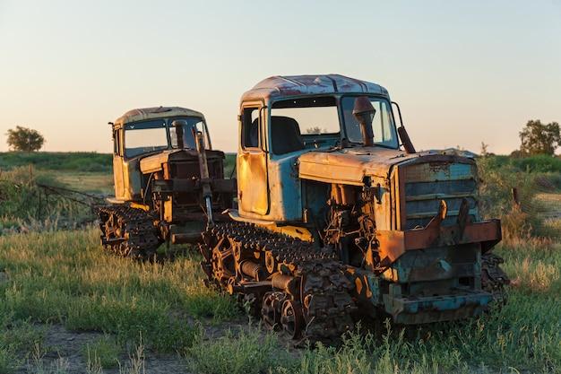 Очень старый ржавый трактор в зеленом поле под голубым небом в летнее время