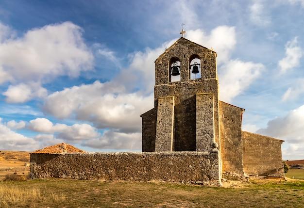 푸른 하늘, 구름과 태양 필드 중간에 아주 오래 된 돌 교회. 농촌 환경. 세고비아