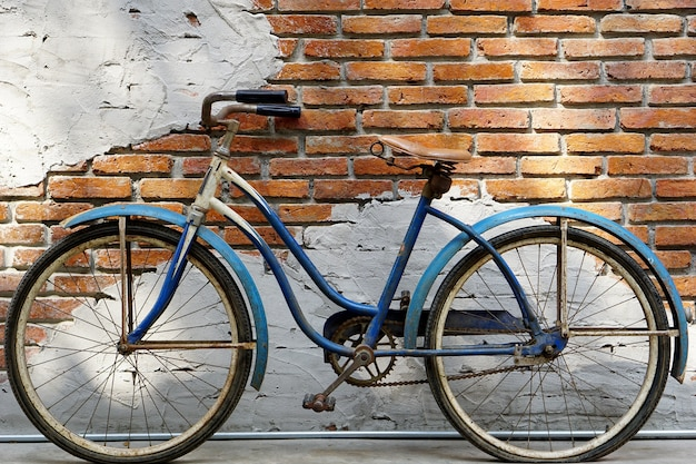 Very old vintage blue bicycle in front of the brick wall