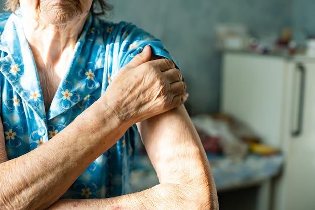 Very old woman holds out her arm for vaccination