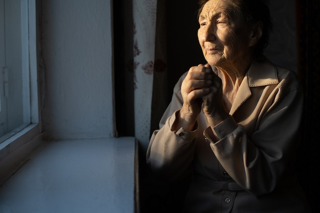 Very old woman is praying in her country style kitchen