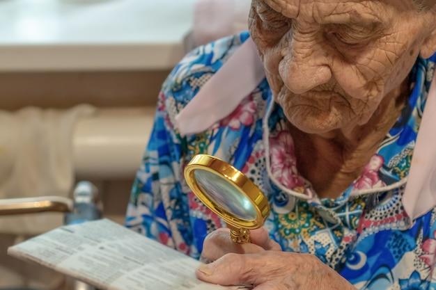 新聞から読み込もうとしている拡大鏡を持つ非常に古い女性
