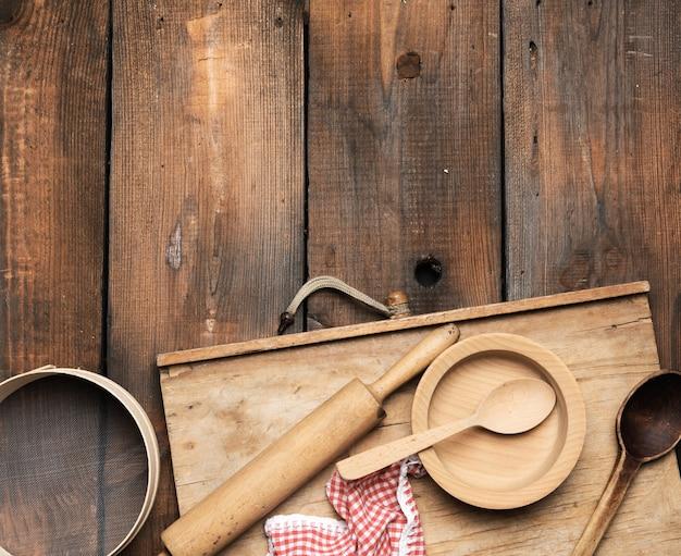Очень старые деревянные кухонные винтажные предметы: сито, скалка, пустые ложки и круглые тарелки на коричневом деревянном столе, вид сверху