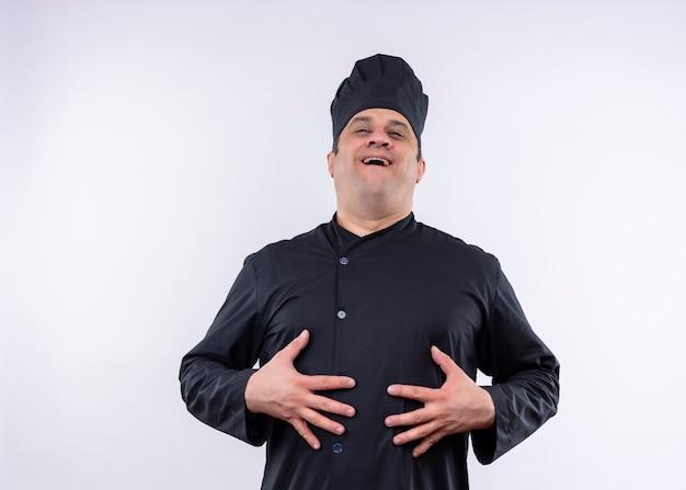 Очень доволен шеф-повар-мужчина в черной униформе и поварской шляпе, улыбаясь, чувствуя положительные эмоции, стоя на белом фоне