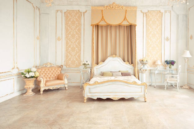 Very rich interior of the apartment with golden decorations on the walls in the baroque style and luxury furniture with gold paint.