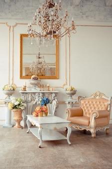 바로크 스타일의 벽면에 금색 장식과 금색 페인트로 된 고급 가구가있는 아파트의 매우 풍부한 인테리어.