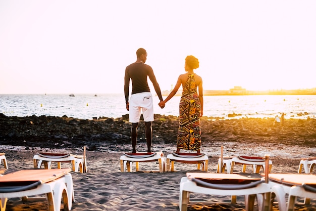 Very romantic black young guys model couple african race hands by hands stand up looking themselves with a sunset in surface. sand beach and seats closed for an infinity love concept