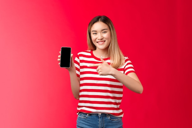 Very satisfied cheerful cute asian blond girl smiling broadly show smartphone display pointing phone...
