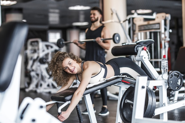 매우 섹시 한 젊은 아름 다운 여자 훈련 및 체육관 클럽에서 가죽 끈에 엉덩이 운동을 하 고