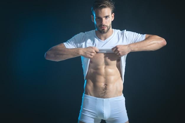 Очень сексуальный молодой человек показывает мышцы живота и снимает футболку, изолированную на черном