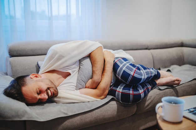 Very sick caucasian man in pajamas and covered with blanket lying on sofa in living room, holding pillow and having stomach ache.