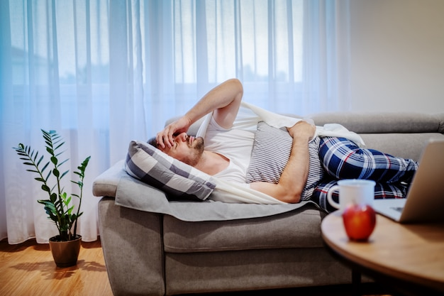 Very sick caucasian man in pajamas and covered with blanket lying on sofa in living room, holding pillow and having stomachache.
