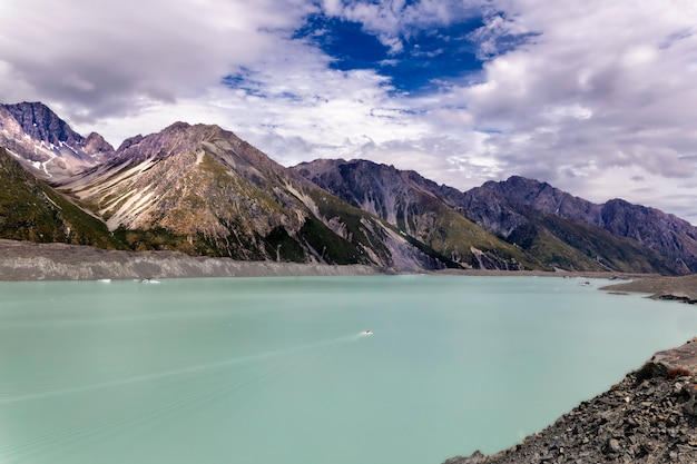 Very small boat in a beautiful turqouise tasman glacier lake and rocky mountains