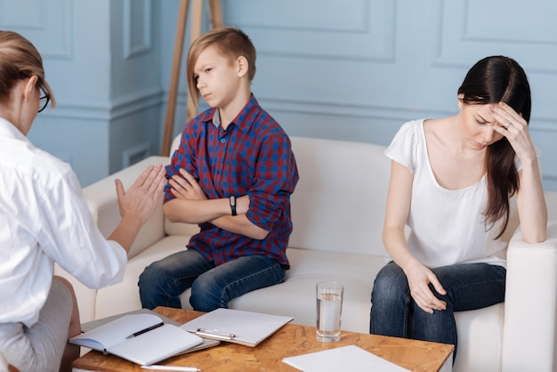 Very stubborn teenager wearing casual clothes having stylish haircut looking angrily on woman