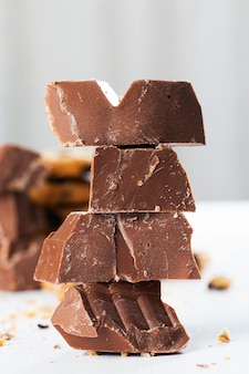 テーブルの上にあるとても甘いチョコレート。壊れたチョコレートとチョコレートドロップと小麦のクッキー