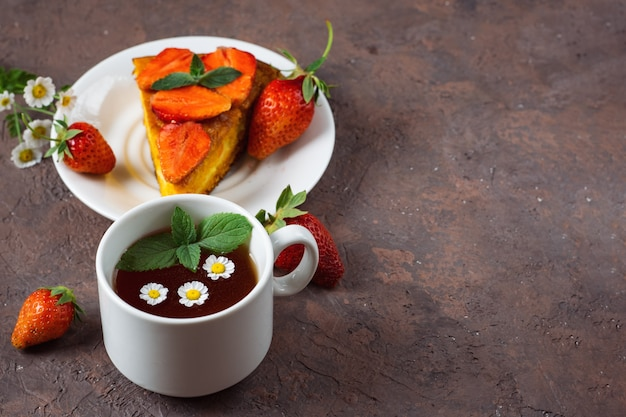 Very tasty carrot cake decorated with strawberries and a cup of fragrant flower tea
