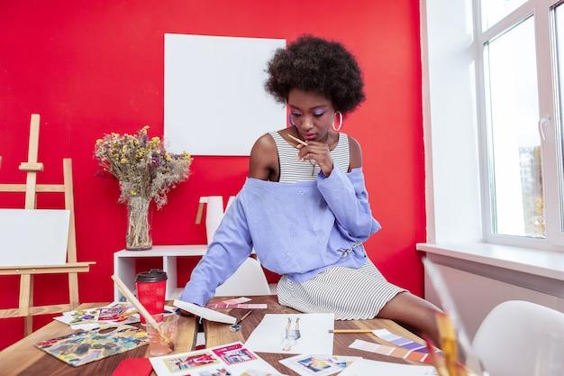 とても思慮深い。彼女の手に鉛筆を持っている黒髪の巻き毛のデザイナーは非常に思慮深い感じ Premium写真