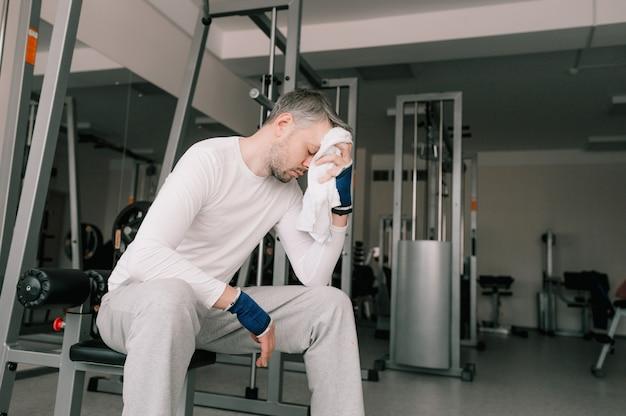 激しいトレーニングの後、非常に疲れた男性がジムに座って、タオルで顔の汗を拭きます。あなたの体の世話をします