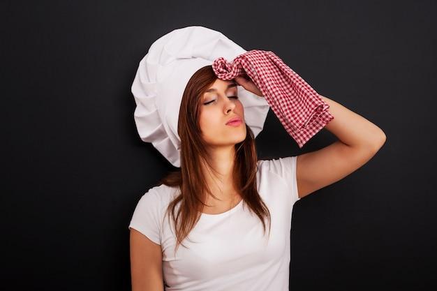 Cuoco unico femminile molto stanco che pulisce il fronte dal sudore