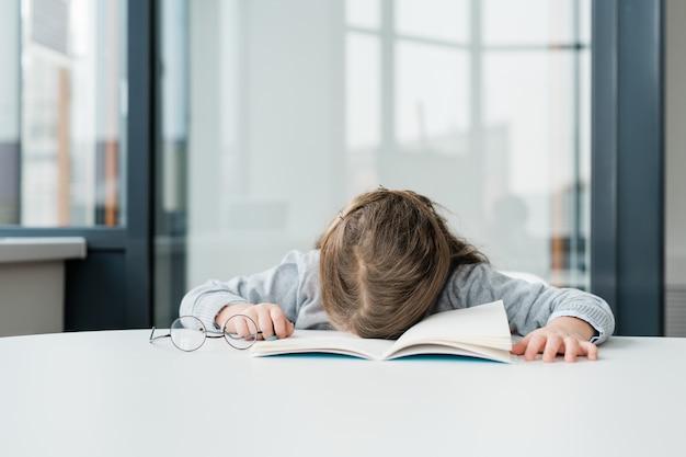 Очень усталая или скучающая школьница в очках дремлет на открытой тетради за партой в классе после урока