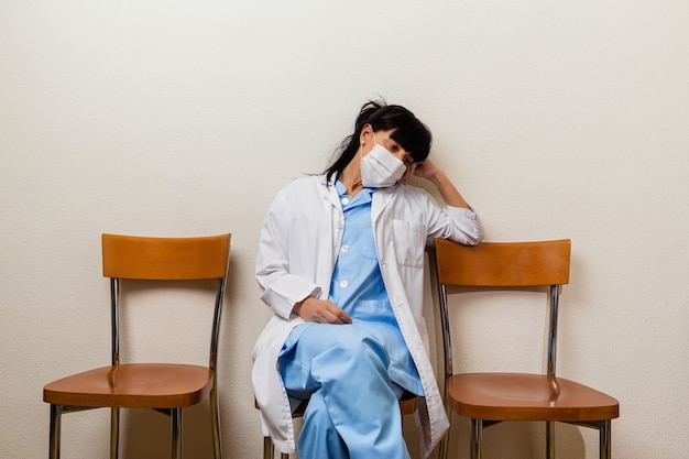 A very tired and pensive nurse sitting in a waiting room after her shift at the hospital.
